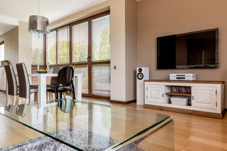 big windows: Cozy modern room with transparent table, dining table, big windows and home cinema with tv Stock Photo
