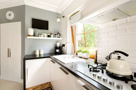 white kitchen: Functional modern white kitchen with cabinets, stove and window Stock Photo