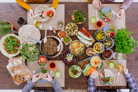 Friends eating colorful vegetarian meal, sitting beside rustic table