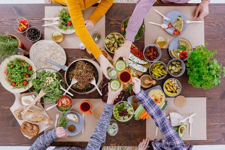 Las personas que se sientan en la mesa rústica, comer alimentos saludables