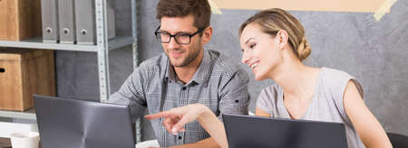 Twee collega's die elkaars documenten raadplegen op de computers in modern bureau