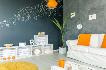 sofa furniture: Apartment with white sofa, blackboard wall and diy furniture Stock Photo