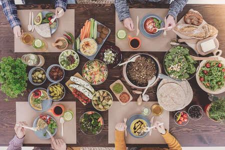 Menschen essen gesundes Mittagessen, sitzen neben rustikalen Tisch
