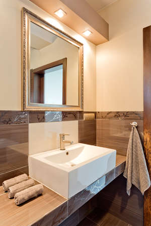 wall mirror: White elegant sink with towels and wall mirror in cozy brown bathroom