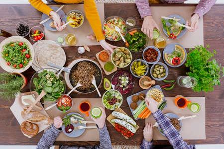 communal: People having veg meal, sitting at wood communal table