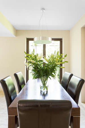 wenge: Wenge dining table, leather chairs, flowers in vase and pendant lamp in bright room with big window