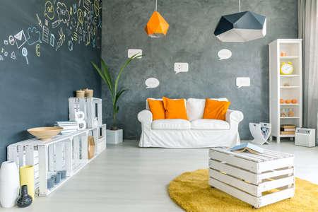 Kamer met krijtbord muur, bank en wit kratmeubels