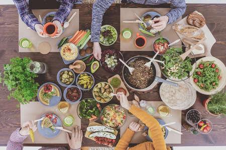 Vegetarier beim Abendessen, sitzen am rustikalen Esstisch