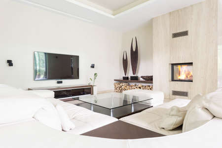 travertine house: Modern bright living room with sofa, glass table, tv set and travertine fireplace Stock Photo