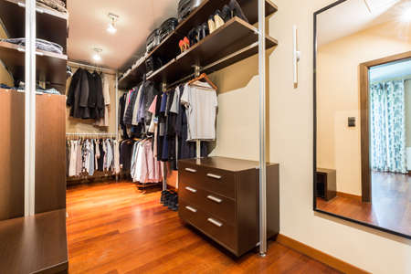 Private spacious walk-in closet full of clothes and shoes with wooden wardrobes