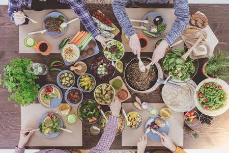 채식 식당에서 가족과 함께하는 저녁 식사를 즐기는 사람들