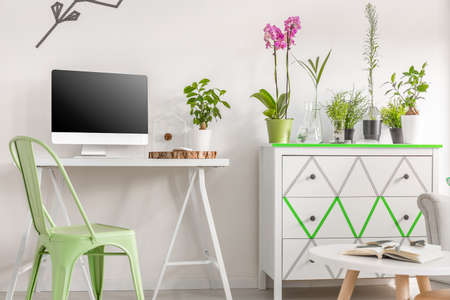 interior shot: Shot of a bright room interior with a white desk and a modern chest of drawers decorated with a washi tape