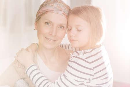 apoyo familiar: Mujer joven con el pañuelo de cáncer que tiene su apoyo a la familia
