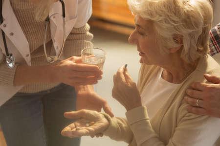 apoyo familiar: Doctor que da medicinas a paciente de alto nivel durante la visita al hogar