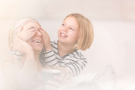 Daughter playing with her sick mother suffering from brain tumor Stock Photo