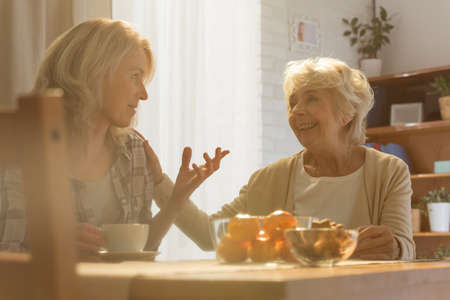 beside table: Woman sitting beside table while talking with her old mother