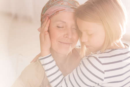 leucemia: Small caring child embracing mother suffering from leukemia