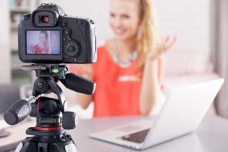 그녀의 방송을 촬영하는 동안 노트북과 책상 옆에 앉아있는 여자