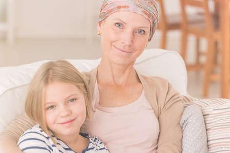 leucemia: Mujer con cáncer sentado en el sofá con su hija