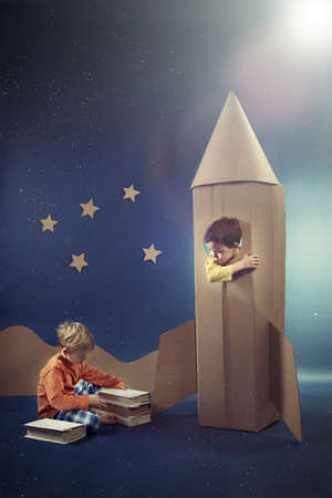visualise: Friends enjoying their dreams with books and rocket Stock Photo