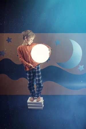 visualise: Boy wearing pyjamas keeping the shining ball Stock Photo