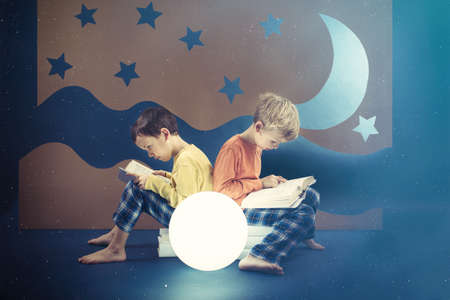 preoccupied: Friends preoccupied by reading books at night Stock Photo