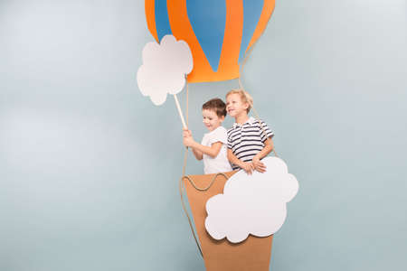 visualise: Young and smiled boys taking a balloon flight Stock Photo