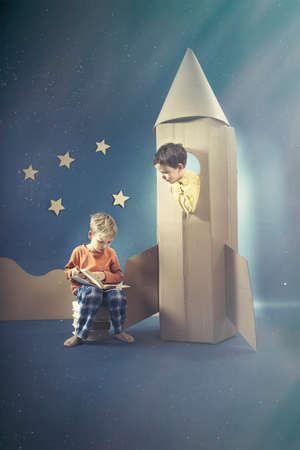 visualise: Boy in rocket looking at his reading friend