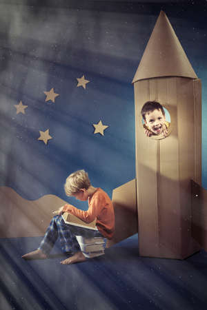 visualise: Boy in paper rocket with friend reading book