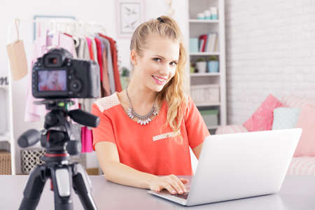 Female vlogger sitting beside desk with laptop, editing her video Stock Photo