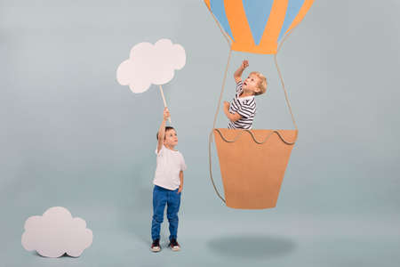 Boy in air balloon pointing the sky