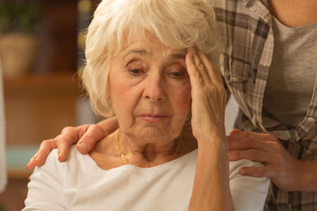 Senior woman feeling discomfort and her caring daughter