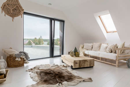 Witte zolderkamer met balkon en houten decoratieve accessoires Stockfoto