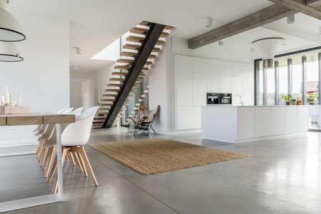 Open verdieping appartement met trap, eettafel en keuken Stockfoto