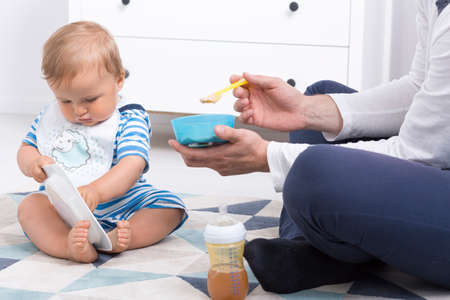 fondness: Close-up of a baby playing with plate during feeding