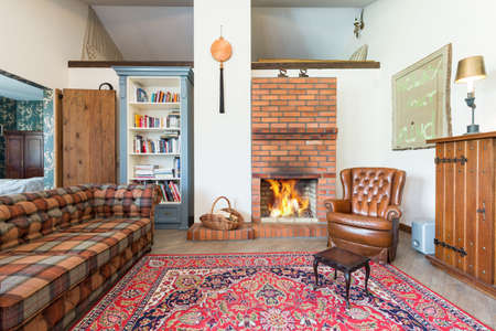 comfort room: Rustic cozy living room with bricked fireplace, couch, armchair and old-fashioned carpet Stock Photo