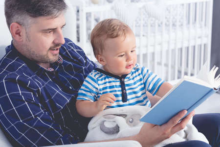 fondness: Father with his baby on his laps reading a book Stock Photo