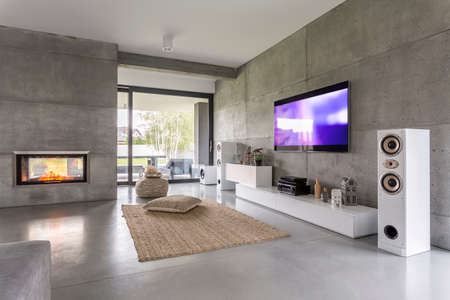 Tv living room with window, fireplace and concrete wall effect Фото со стока - 68553695