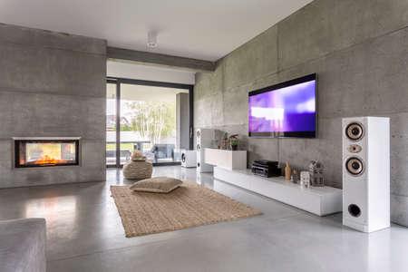 TV woonkamer met raam, open haard en betonnen muur effect