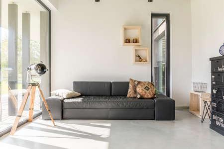 salón blanco con muebles de color negro y la ventana Foto de archivo