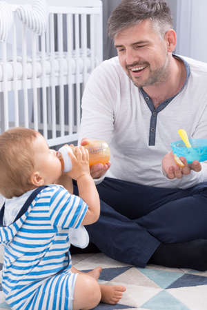 fondness: View of a dad and his baby sitting on a floor during nursing Stock Photo