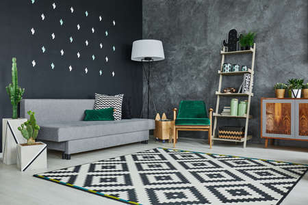 Grey room with blackboard wall, cactus and sofa Фото со стока