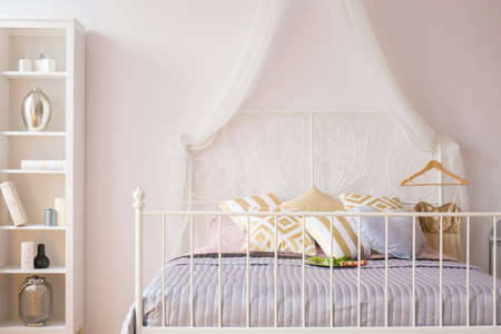 canopy: Room with bed with metal headboard and white bookcase