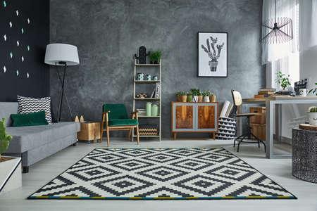 Grijze kamer met patroon tapijt en houten meubilair