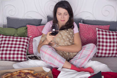 parting: Depressed woman sitting on couch, crying and drinking wine