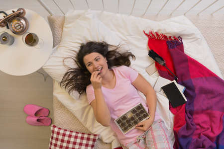 ベッドで横になっているとチョコレートを食べる幸せの独身女性 写真素材