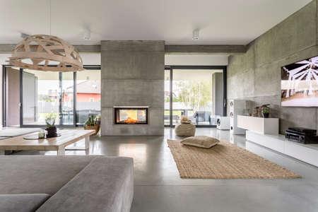 Ruim villa interieur met cement muur effect, open haard en tv Stockfoto