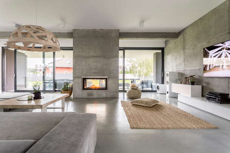 Spacious villa interior with cement wall effect, fireplace and tv Фото со стока - 68553748