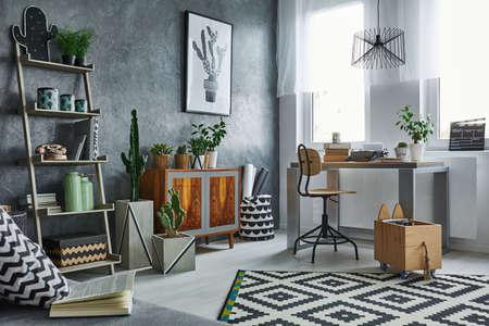 Functional flat in grey with bookshelf, desk and chair 版權商用圖片