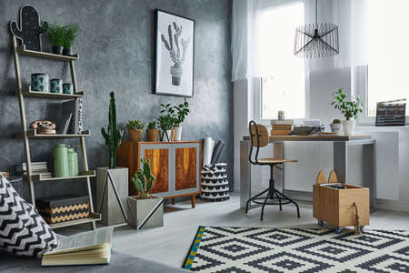 Functionele flat in grijs met boekenkast, bureau en een stoel